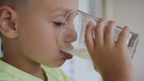 Κινηματογράφηση σε πρώτο πλάνο Το καλό αγόρι πίνει το φρέσκο γάλα και παίρνει το γάλα moustache, απομονωμένος στο άσπρο υπόβαθρο  απόθεμα βίντεο