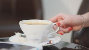 Κινηματογράφηση σε πρώτο πλάνο Το κορίτσι σε ένα άσπρο πουκάμισο κρατά ένα φλυτζάνι του καυτού καφέ στην κορυφή με μια κτυπημένη  απόθεμα βίντεο