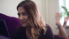 Κινηματογράφηση σε πρώτο πλάνο Το όμορφο νέο κορίτσι απολαμβάνει μια ταμπλέτα στον καναπέ Εγχώριο ύφος απόθεμα βίντεο