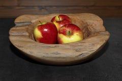 Κινηματογράφηση σε πρώτο πλάνο τριών μήλων σε ένα ξύλινο κύπελλο στοκ εικόνες