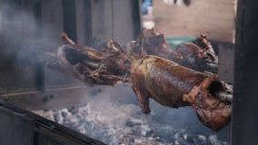 Κινηματογράφηση σε πρώτο πλάνο τριών σφαγίων του χοιρινού κρέατος που καπνίζονται σε έναν περιστρεφόμενο οβελό απόθεμα βίντεο