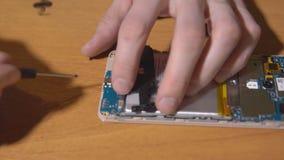 Κινηματογράφηση σε πρώτο πλάνο των ανθρώπινων χεριών που επισκευάζουν ένα κινητό τηλέφωνο απόθεμα βίντεο