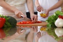 Κινηματογράφηση σε πρώτο πλάνο των ανθρώπινων χεριών που μαγειρεύουν στην κουζίνα Θηλυκό τέμνον κουδουνιών δύο πιπέρι μητέρων και στοκ εικόνες