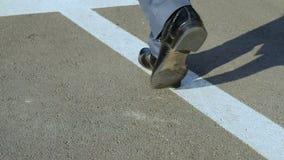 Κινηματογράφηση σε πρώτο πλάνο των αρσενικών ποδιών που περπατούν κατά μήκος του βέλους, ξεκίνημα, πορεία του φιλόδοξου ηγέτη απόθεμα βίντεο