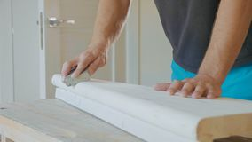 Κινηματογράφηση σε πρώτο πλάνο των αρσενικών χεριών που γυαλίζουν το ξύλινο βήμα με το γυαλόχαρτο Στοκ Εικόνα