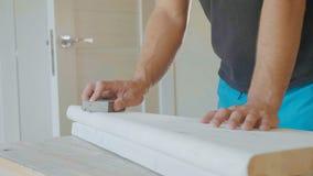 Κινηματογράφηση σε πρώτο πλάνο των αρσενικών χεριών που γυαλίζουν το ξύλινο βήμα με το γυαλόχαρτο Στοκ εικόνες με δικαίωμα ελεύθερης χρήσης