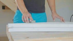 Κινηματογράφηση σε πρώτο πλάνο των αρσενικών χεριών που γυαλίζουν το ξύλινο βήμα με το γυαλόχαρτο Στοκ φωτογραφία με δικαίωμα ελεύθερης χρήσης