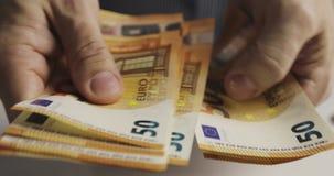 Κινηματογράφηση σε πρώτο πλάνο των αρσενικών χεριών που μετρούν ένα πακέτο πενήντα ευρο- λογαριασμών απόθεμα βίντεο