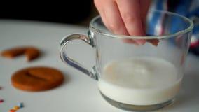 Κινηματογράφηση σε πρώτο πλάνο των βυθίζοντας μπισκότων παιδιών στο γάλα απόθεμα βίντεο