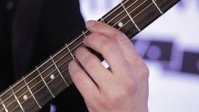 Κινηματογράφηση σε πρώτο πλάνο των δάχτυλων που ρυθμίζουν εκ νέου τις χορδές στην ακουστική κιθάρα φιλμ μικρού μήκους