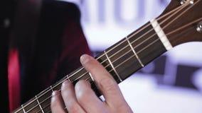 Κινηματογράφηση σε πρώτο πλάνο των δάχτυλων που ρυθμίζουν εκ νέου τις χορδές στην ακουστική κιθάρα απόθεμα βίντεο