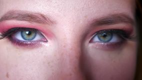 Κινηματογράφηση σε πρώτο πλάνο των ελκυστικών θηλυκών μπλε ματιών makeup με τις ρόδινες σκιές και το γοητευτικό eyeline που εξετά φιλμ μικρού μήκους