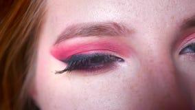 Κινηματογράφηση σε πρώτο πλάνο των ελκυστικών θηλυκών μπλε ματιών makeup με τις ρόδινες σκιές και το όμορφο eyeline που εξετάζουν απόθεμα βίντεο