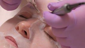 Κινηματογράφηση σε πρώτο πλάνο των επαγγελματικών χεριών beautician σχετικά με το θηλυκό μέτωπο με τον εξοπλισμό για Microcurrent απόθεμα βίντεο