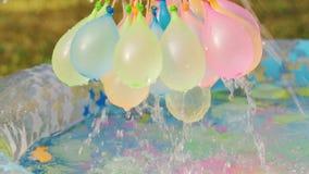 Κινηματογράφηση σε πρώτο πλάνο των ζωηρόχρωμων μπαλονιών νερού που γεμίζουν με το νερό τη θερινή ημέρα φιλμ μικρού μήκους
