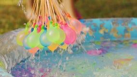Κινηματογράφηση σε πρώτο πλάνο των ζωηρόχρωμων μπαλονιών νερού που γεμίζουν με το νερό τη θερινή ημέρα απόθεμα βίντεο