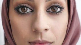 Κινηματογράφηση σε πρώτο πλάνο των θηλυκών ινδικών λυπημένων ματιών Νέο όμορφο σοβαρό ινδικό κορίτσι στο ρόδινο hijab που εξετάζε φιλμ μικρού μήκους