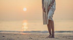 Κινηματογράφηση σε πρώτο πλάνο των θηλυκών ποδιών στην παραλία πρωινού Νέο σύγχρονο κορίτσι σε μια μακριά φούστα που στέκεται στο στοκ φωτογραφία με δικαίωμα ελεύθερης χρήσης