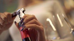 Κινηματογράφηση σε πρώτο πλάνο των θηλυκών χεριών που ένα μπουκάλι του κρασιού Κορίτσι που το κρασί με ένα ανοιχτήρι φιλμ μικρού μήκους