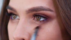 Κινηματογράφηση σε πρώτο πλάνο των ματιών smokey makeup για τη νέα γυναίκα σε σε αργή κίνηση απόθεμα βίντεο