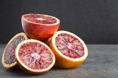 Κινηματογράφηση σε πρώτο πλάνο των μισών των αιματηρών πορτοκαλιών στον γκρίζο πίνακα στο μαύρο κλίμα Φρέσκα σισιλιάνα πορτοκάλια στοκ φωτογραφία