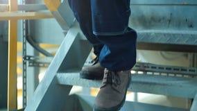 Κινηματογράφηση σε πρώτο πλάνο των μποτών εργαζομένων ` s που περπατούν στο βαρύ εργοστάσιο βιομηχανίας απόθεμα βίντεο