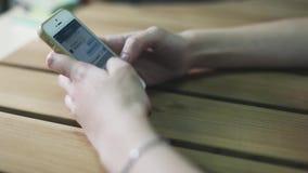 Κινηματογράφηση σε πρώτο πλάνο των νέων χεριών γυναικών που δακτυλογραφούν και που τυλίγουν τα κοινωνικά μέσα αγγελιοφόρων απόθεμα βίντεο
