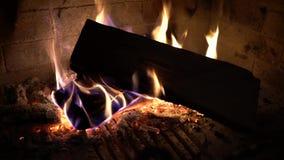 Κινηματογράφηση σε πρώτο πλάνο των ξύλινων κούτσουρων που καίνε στην παραδοσιακή εστία στο σκοτάδι απόθεμα βίντεο