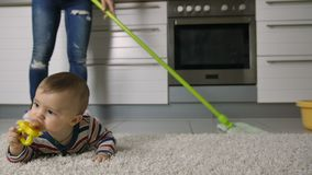 Κινηματογράφηση σε πρώτο πλάνο των ποδιών γυναικών ` s που καθαρίζουν το πάτωμα κοντά στο μωρό απόθεμα βίντεο