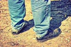 Κινηματογράφηση σε πρώτο πλάνο των ποδιών ενός ατόμου στο παλαιό τζιν παντελόνι και τα καταπονημένα παπούτσια Τ Στοκ Φωτογραφία