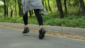Κινηματογράφηση σε πρώτο πλάνο των ποδιών που τρέχουν το κορίτσι μέσω ενός πάρκου φθινοπώρου απόθεμα βίντεο