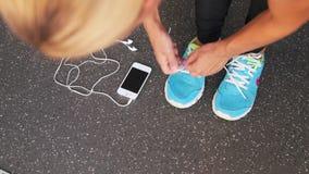 Κινηματογράφηση σε πρώτο πλάνο των ποδιών του θηλυκού δρομέα που παίρνουν τα έτοιμα δένοντας τρέχοντας παπούτσια με το smartwatch απόθεμα βίντεο