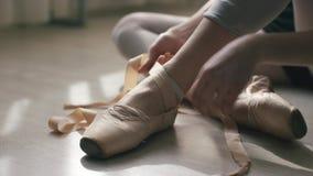 Κινηματογράφηση σε πρώτο πλάνο των ποδιών του ballerina σε ένα ελαφρύ ξύλινο πάτωμα Δένοντας κορδέλλα κοριτσιών των παπουτσιών po απόθεμα βίντεο