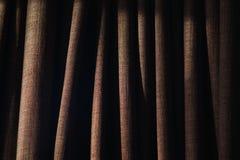 Κινηματογράφηση σε πρώτο πλάνο των πτυχών στην κουρτίνα με το δευτερεύοντα φωτισμό στοκ εικόνα