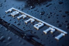 Κινηματογράφηση σε πρώτο πλάνο των πτώσεων βροχής στο μαύρο λογότυπο ferrari Στοκ Φωτογραφία