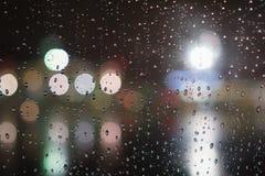 Κινηματογράφηση σε πρώτο πλάνο των σταγόνων βροχής στο παράθυρο στη νύχτα με τα φω'τα Στοκ Εικόνα