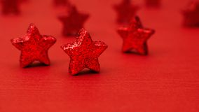 Κινηματογράφηση σε πρώτο πλάνο των σύγχρονων κόκκινων ακτινοβολώντας αστεριών Χριστουγέννων που στέκονται σε έναν κόκκινο πίνακα Στοκ φωτογραφία με δικαίωμα ελεύθερης χρήσης