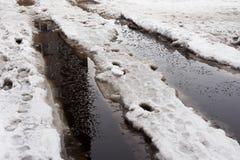 Κινηματογράφηση σε πρώτο πλάνο των τεράστιων λακκουβών του χιονιού στις οδούς πόλεων στοκ εικόνες
