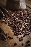Κινηματογράφηση σε πρώτο πλάνο των φασολιών καφέ στο ξύλινο υπόβαθρο στοκ εικόνες