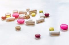 Κινηματογράφηση σε πρώτο πλάνο των χαπιών στο άσπρο υπόβαθρο, το φάρμακο και τα χάπια καψών στο πάτωμα Στοκ Εικόνες