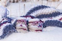 Κινηματογράφηση σε πρώτο πλάνο των χειροποίητων πλεκτών μάλλινων λειών μωρών στο χιόνι Στοκ εικόνες με δικαίωμα ελεύθερης χρήσης