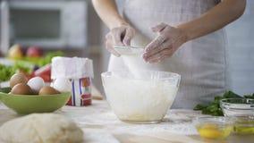 Κινηματογράφηση σε πρώτο πλάνο των χεριών γυναικών που κοσκινίζουν το αλεύρι πέρα από το κύπελλο γυαλιού με τη ζύμη, αρτοποιείο φιλμ μικρού μήκους