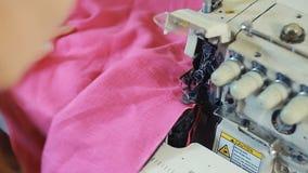 Κινηματογράφηση σε πρώτο πλάνο των χεριών γυναικών ` s που ράβουν ένα overlock στη ράβοντας μηχανή απόθεμα βίντεο