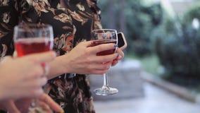 Κινηματογράφηση σε πρώτο πλάνο των χεριών δύο γυναικών με τα ποτήρια του κόκκινου κρασιού απόθεμα βίντεο