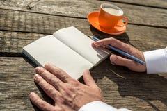 Κινηματογράφηση σε πρώτο πλάνο των χεριών ενός ατόμου έτοιμου να γράψει μπροστά από έναν ανοικτό Στοκ Εικόνες