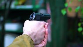 Κινηματογράφηση σε πρώτο πλάνο των χεριών ενός ατόμου που κάνει ένα πυροβόλο όπλο δύο πυροβολισμούς απόθεμα βίντεο