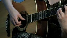 Κινηματογράφηση σε πρώτο πλάνο των χεριών ενός κοριτσιού που παίζει μια ακουστική κιθάρα Εστίαση στα δάχτυλα που στερεώνουν τις χ απόθεμα βίντεο