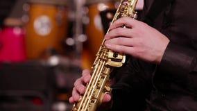 Κινηματογράφηση σε πρώτο πλάνο των χεριών ενός saxophonist σε ένα saxophone σοπράνο Ένας μουσικός σε ένα μαύρο πουκάμισο παίζει τ φιλμ μικρού μήκους