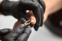 Κινηματογράφηση σε πρώτο πλάνο των χεριών μανικιουριστών που αφαιρούν την επιδερμίδα με τους νυχοκόπτες από τα νύχια πελατών στοκ εικόνα