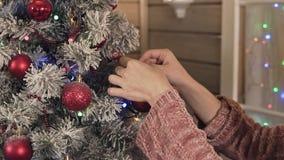 Κινηματογράφηση σε πρώτο πλάνο των χεριών νέων κοριτσιών που διακοσμούν το χριστουγεννιάτικο δέντρο από τις κόκκινες σφαίρες απόθεμα βίντεο